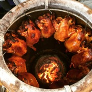 Whole chickens cooking in large metal vessels